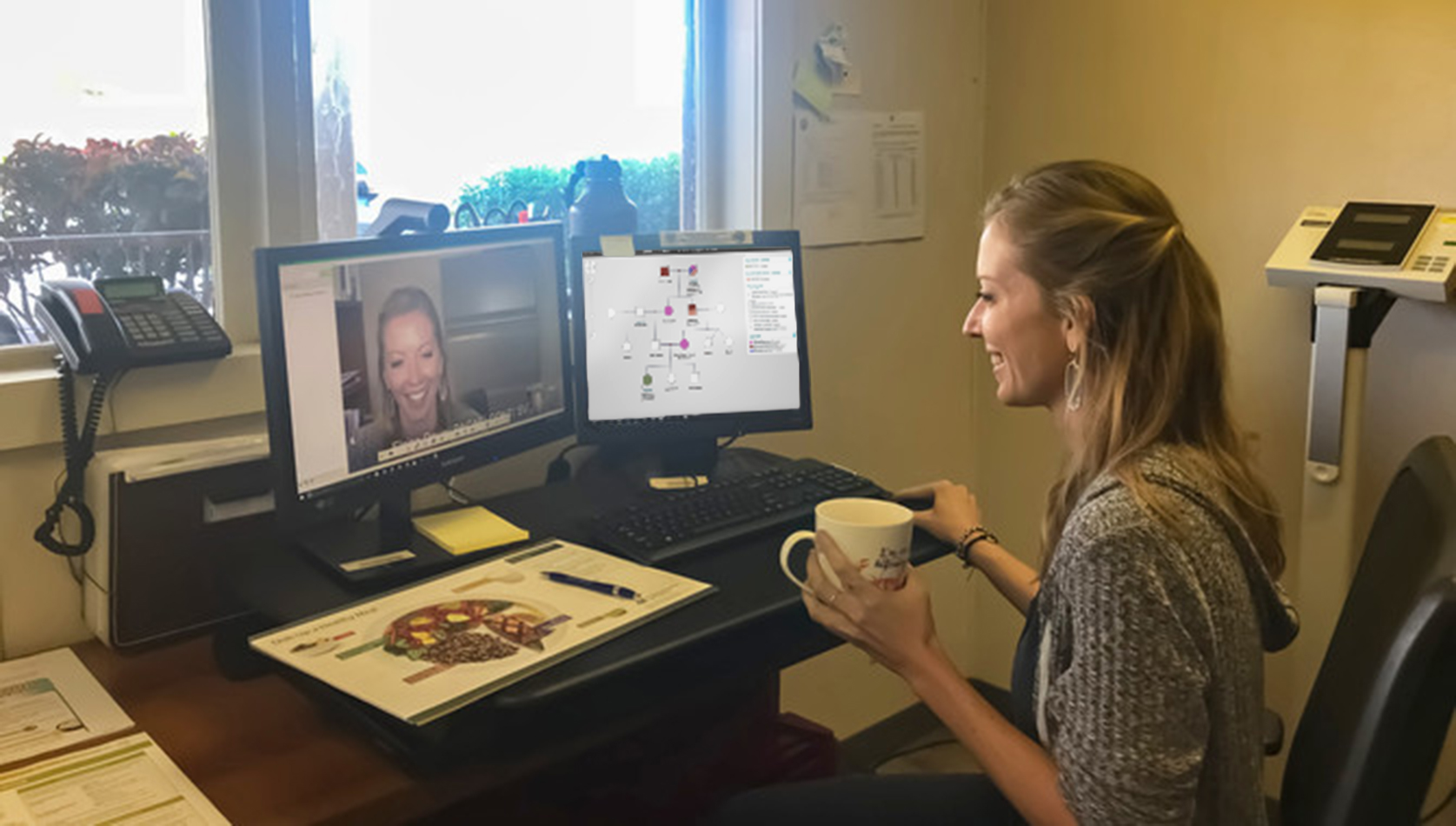 A woman sits at her home office desk holding a cup of tea. She smiles and holds a mouse while looking at one of two monitors on her desk. One monitor shows she's on a video call, the other has an open PhenoTips pedigree.